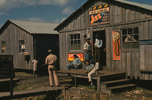 "Living quarters and ""juke joint"" for migratory workers, a slack season; Belle Glade, Fla. Wolcott, Marion Post, 1910- photographer. CREATED/PUBLISHED: 1941 Feb. SUMMARY: Photograph shows man standing to left with gun. Signs advertise Ice Cold Jax Ale Beer Stout and Ice Cold Coca Cola. MEDIUM: 1 slide : color. CALL NUMBER: LC-USF35-173   http://memory.loc.gov/ammem/fsahtml/fahome.html"