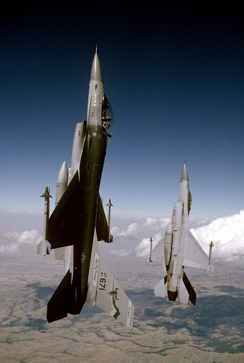 Armed with AIM-9 Sidewinder missiles, a pair of F-16A Fighting Falcon aircraft of the 120th Fighter Interceptor Group, Montana Air National Guard, climb skyward at a 90 degree angle while flying a mission near Great Falls International Airport.