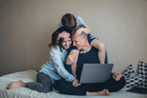 זוג צעיר מחפש דירות בהרצליה עם מחשב על המיטה